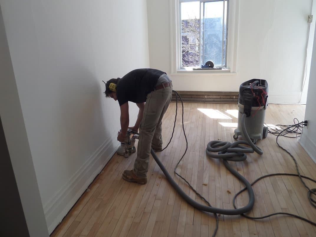 Employé en train de poncer un plancher